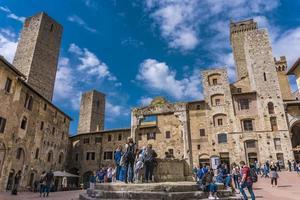 SAN GIMIGNANO, ITALY, APRIL 8, 2018 - Unidentified people at Piazza della Cisterna in San Gimignano, Italy. Historic Centre of San Gimignano is designated as UNESCO World Heritage Site since 1990. photo