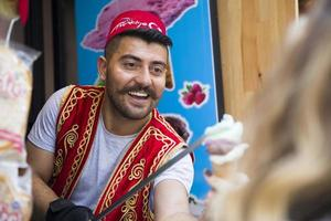 ISTANBUL, TURKEY, JUNE 15, 2019 - Unidentified seller of Turkish ice cream at Istanbul, Turkey. Traditional Turkish ice cream was made with salep, produced by orchid flowers. photo