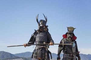 miyajima, japón, 10 de octubre de 2016 - hombres no identificados vestidos como samuráis en el santuario de itsukushima en la isla de muyajima, japón. santuario es un sitio del patrimonio mundial de la unesco desde 1996. foto