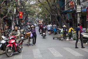HANOI, VIETNAM, MARCH 2, 2017 - Unidentified people on the street of Hanoi, Vietnam. At Hanoi, motorbikes have overtaken bicycles as the main form of transportation. photo