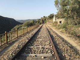 Abandoned railroad tracks through the mountains photo