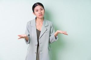 Young Asian businesswoman wearing green suit on green background photo