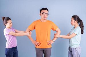 Three young Asian people posing on blue background photo