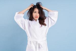 Young Asian woman wearing bathrobe on blue background photo