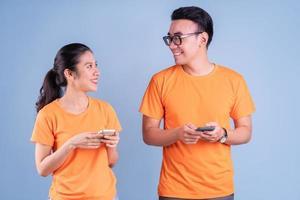 Joven pareja asiática vistiendo camiseta naranja sobre fondo azul. foto