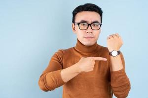 Asian man looking his watch on blue background photo
