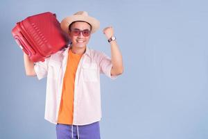 Young Asian man holding red suitcase on blue background photo