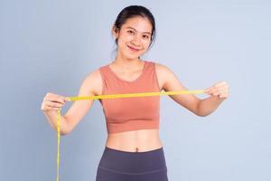 Hermosa mujer asiática vistiendo ropa deportiva y haciendo yoga, fitness y concepto de gimnasio foto