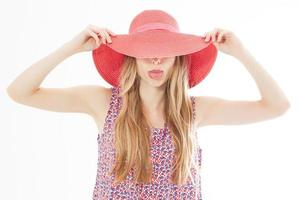 Beautiful attractive girl hides her face behind her summer hat and shows her tongue isolated over white. photo