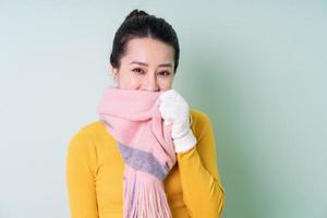 Beautiful young Asian woman wearing sweater on green background photo