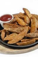 spicy curry powder coated crispy deep fried potato wedges photo