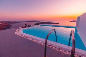 Infinity pool on the rooftop at sunset in Santorini Island, Greece. Beautiful poolside and sunset sky. Luxurious summer vacation and holiday concept, romantic scenery and evening view photo