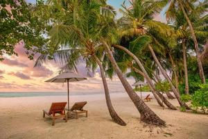 Romantic tropical sunset scenery, two sun beds, loungers, umbrella under palm tree. White sand, sea view with horizon, colorful twilight sky, calmness and relaxation. Inspirational beach resort hotel photo