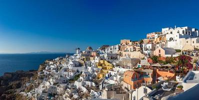 Famous view of Oia town cityscape at Santorini island in Greece. Traditional blue dome and white houses. Greece, Aegean sea. Famous European destination photo