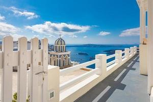 Travel landscape of sunny Santorini, Greece. White architecture in Oia on Santorini. Greece. Summer vacation scenery, white fence, caldera sea view cruise ships. Island bay, shore, idyllic blue sky photo
