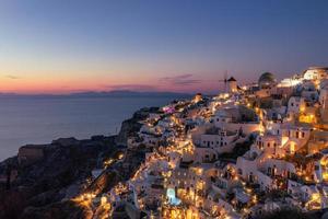 hermosa puesta de sol isla de santorini grecia, hermoso pueblo encalado iglesia de oia y molino de viento durante la puesta de sol, luces de las calles, románticas vacaciones de verano, famoso destino de viaje de pareja de luna de miel foto