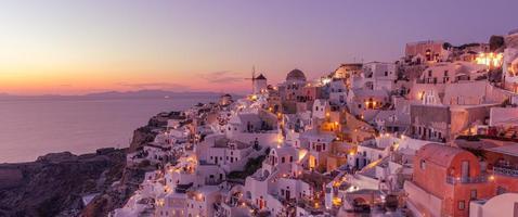 hermosa puesta de sol isla de santorini grecia, hermoso pueblo encalado oia con molino de viento de la iglesia durante la puesta de sol, luces de las calles, románticas vacaciones de verano, famoso destino de viaje de pareja de luna de miel foto