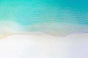 Summer seascape beautiful waves, blue sea water in sunny day. Top view from drone. Sea aerial view, amazing tropical nature background. Beautiful bright sea with waves splashing and beach sand concept photo