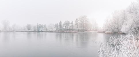 Winter forest on the river at sunset. Panoramic landscape with snowy trees, sun, beautiful frozen river with reflection in water. Seasonal. Winter trees, lake and blue sky. Frosty snowy river. Weather photo