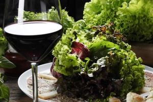 Carpaccio, parmesan, lettuce and red wine photo