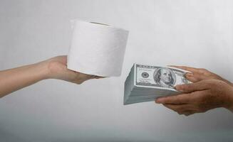 Cerrar vender comprar pañuelos desechables, mano sostiene papel higiénico y dinero de 100 dólares en billetes mucho, es decir, cuesta un precio caro y productos de alto precio. foto