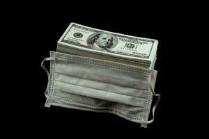 máscara de médico y protección contra virus y dinero una pila de billetes de 100 dólares estadounidenses mucho en el fondo negro, es decir, cuesta un precio caro y un concepto de productos de alto precio foto