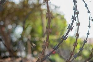 Close-up fence with barbed wire against a blurred background photo