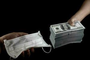 Cerrar vender comprar mascarilla médica, mano sosteniendo máscaras médicas protección contra virus y dinero de billetes de 100 dólares estadounidenses mucho en fondo negro, cuesta productos caros y de alto precio concepto foto
