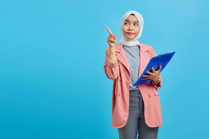 Portrait of a beautiful smiling woman holding a folder standing and pointing to an empty space on a blue background photo