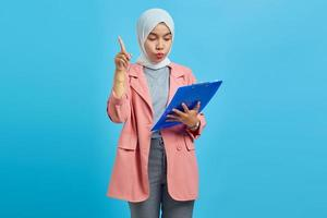 Portrait of a beautiful woman holding a clipboard standing and pointing up on blue background photo