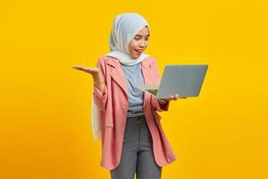 Portrait of cheerful young Asian woman holding laptop and pointing isolated over yellow background photo