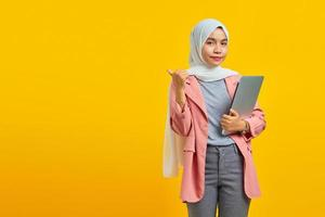 Portrait of a cheerful asian woman holding laptop and pointing to empty space isolated over yellow background photo