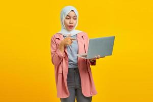 Portrait of excited young Asian woman holding laptop and pointing isolated over yellow background photo
