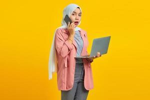 Retrato de mujer asiática sorprendida y conmocionada hablando por teléfono inteligente mientras sostiene el portátil plateado aislado sobre fondo amarillo foto