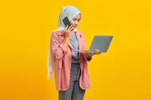Retrato de mujer asiática sonriendo ang hablando por teléfono inteligente mientras sostiene el portátil plateado aislado sobre fondo amarillo foto