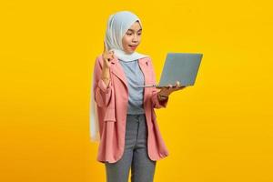 Portrait of excited young Asian woman holding laptop and pointing up isolated over yellow background photo