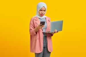 Angry young woman using laptop and mobile phone while standing isolated on yellow background photo