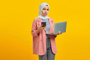 Angry and unhappy young Asian woman holding mobile phone and laptop on blue background photo