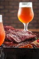 Filete de Denver a la parrilla cortado en rodajas sobre una tabla de cortar de madera con sal parrilla y dos vasos de cerveza sudorosos. carne de vacuno de mármol - primer plano. foto