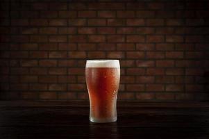 aislado sudoroso vaso de refrescante cerveza de barril ale ámbar con fondo de pared de ladrillo. foto