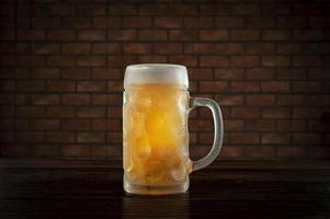 Isolated sweaty glass of refreshing amber ale draft beer with brick wall background. photo