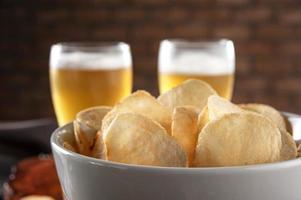 papas fritas en un recipiente con dos vasos de cerveza foto