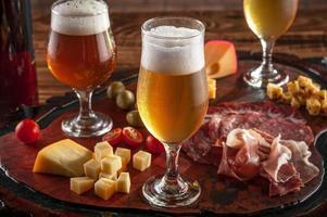 Plato frío con cerveza de barril sobre una tabla para cortar madera foto