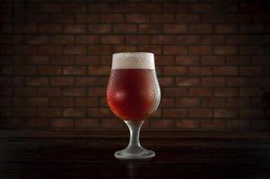 Tulipa sudoroso aislado vaso de refrescante cerveza de barril ale ámbar con fondo de pared de ladrillo. foto