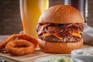 deliciosa hamburguesa de tocino con aros de cebolla y cerveza. foto
