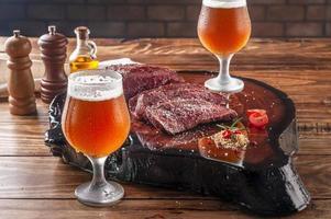 Filete de Denver a la parrilla sobre tabla de cortar de madera con dos vasos de tulipa fría sudorosa de cerveza de barril. carne de vacuno de mármol. foto