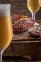 Filete de lomo de tapa en rodajas a la parrilla con dos vasos de cerveza en la tabla de cortar de madera. carne de mármol carne de res - picanha brasileña. foto