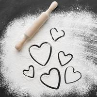 flat lay heart shapes flour with rolling pin photo