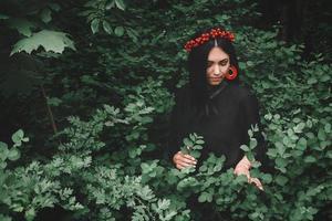 hermosa chica en vestido negro y adornos rojos que sostiene una ramita en su mano contra el fondo del bosque. espacio para su mensaje de texto o contenido promocional foto
