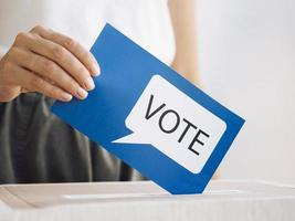 front view woman putting voting message box close up photo